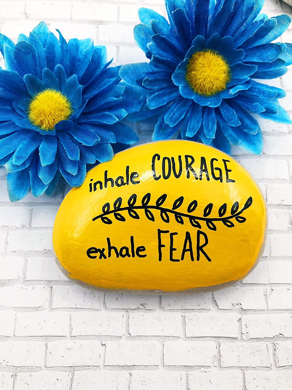 "Yellow rock painted with the phrase ""inhale courage, exhale fear"" in black paint"