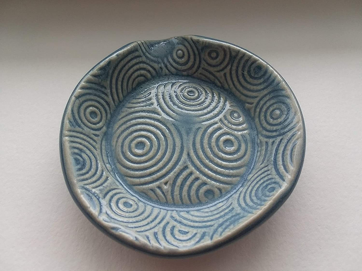 light blue teaspoon rest with stripped or circular patterns