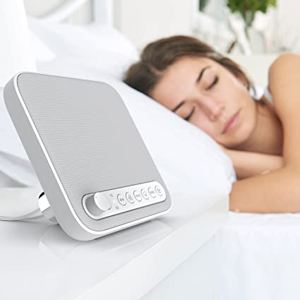 A woman sleeping using a white noise machine.