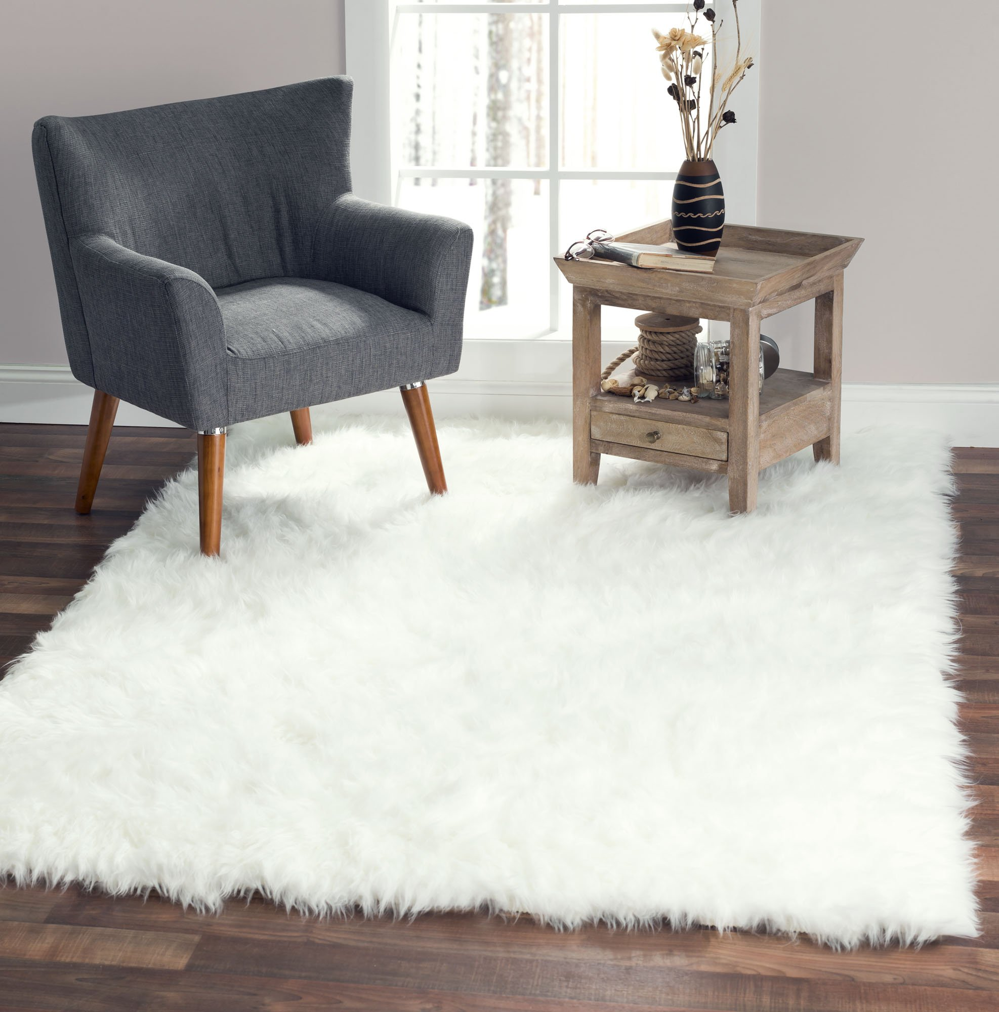 """Softest French White Sheepskin Faux Fur Shag Rug Looks Real, NO Animal Cruelty. Perfect for Photographers Designers or Your Bedroom Living Room or Nursery Made in France 5x7 (55 inches x 79 inches) - OOOH LA LA – FLUFFIEST, PLUSHEST HIGH PILE Faux Sheepskin Rug: If you're looking for the SILKIEST, SOFTEST rugs for your living room – a sheep skin area rug so plush it MAKES YOU FEEL LIKE YOU'RE PETTING an ARCTIC POLAR BEAR - then you'll want to consider this 5x7 rug a top contender. Just look at the reviews and you'll quickly discover why customers say, """"THE PICTURES DON'T DO IT JUSTICE!"""" It's GORGEOUS and piled just high enough to make it enjoyable to lounge on, without the tricky clean-up. FEELS & LOOKS AUTHENTIC, WITHOUT THE CRUELTY: Remember the last time you walked into a space and it felt…well…perfect? Fashion-forward thinkers realize how that one item, one unique thing, and in this case one genuine looking sheepskin shag carpet easily PULLS YOUR DECOR TOGETHER – giving it a wealthy, luxurious ambiance, WITHOUT THE GUILT of harming sweet little animals. STYLISH YET SIMPLE – THE TOP CHOICE of PHOTOGRAPHY STUDIOS & INTERIOR DESIGNERS: If you've done you research you already know that no shaggy rug holds a candle to ours – with more 5-star reviews from professional photographers than any other it's no wonder our shag area rugs are top sellers among those who appreciate FINE DETAIL and only choose the best. And they love how it WON'T PEEL, SHED EXCESSIVELY or CURL UP AT THE ENDS, GUARANTEED! - living-room-soft-furnishings, living-room, area-rugs - 81f5H5V8pOL -"""