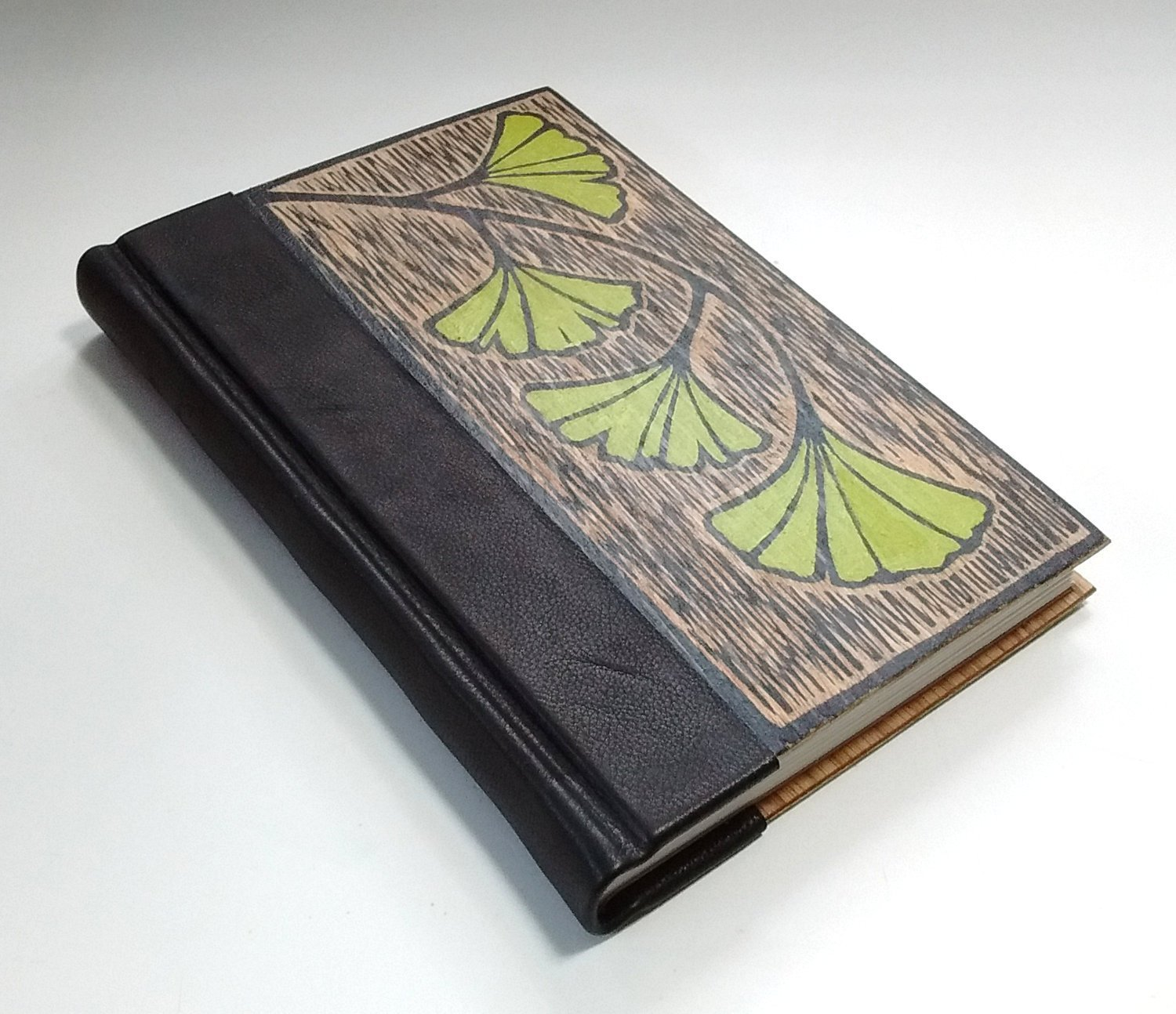 Hand-made book, bound in wood and leather, with original ginkgo art on cover