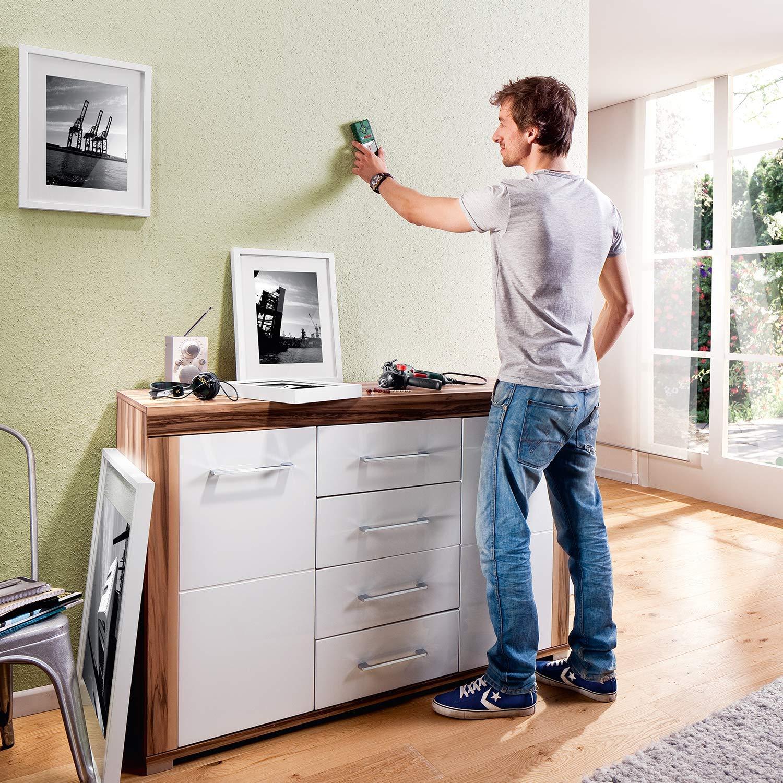 Junger Mann mit Ortungsgerät sucht in seiner Wand nach Leitungen