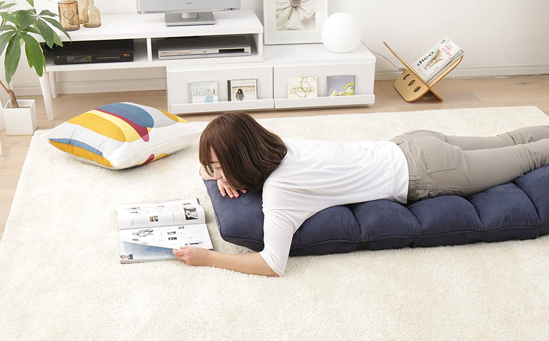 座椅子の背もたれを下げて寝転がる女性