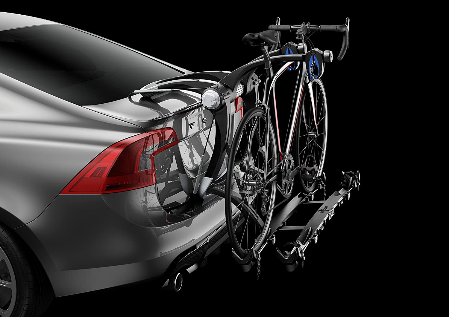 Photo of a bike attached to a rack mounted on the car's trunk, on a black background.