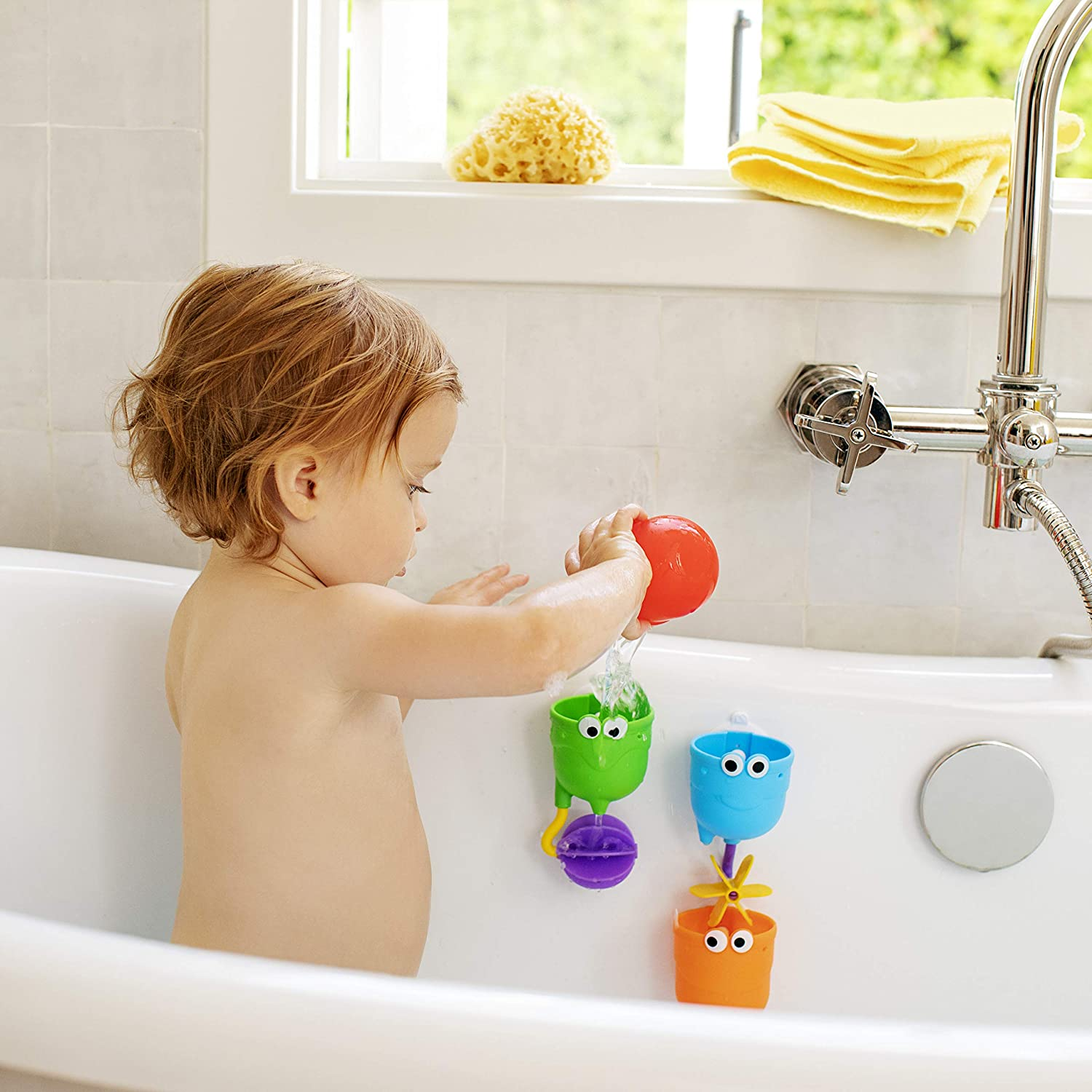toddler playing with munchkin falls bath toys