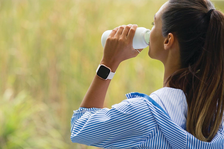 frau mit smartwatch trinkt wasser nach sport in der natur