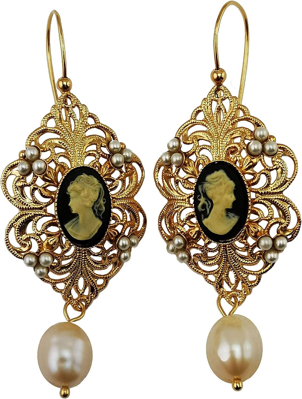 Pendientes Mokilu de latón hipoalergénico con efecto dorado envejecido florentino. Esmalte con cierre de gancho. Dos camafeos de color negro, pequeñas perlas de color marfil y dos perlas naturales.