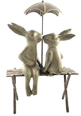 two bunnies on bench under umbrella statue