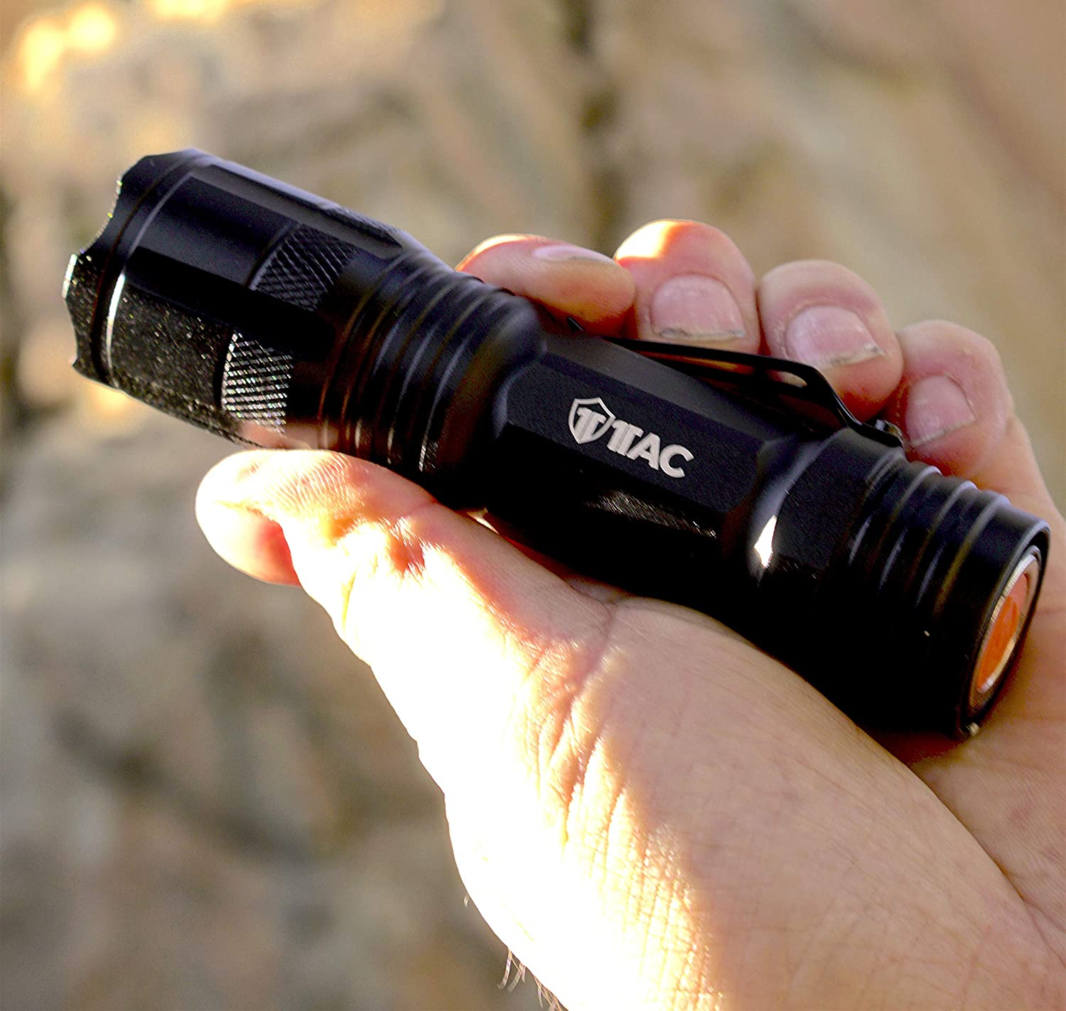 Image of a hand holding a tactical flashlight.
