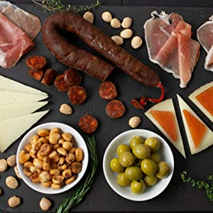 A Little Bit of Spain In A Gift Box - Includes: Jamon Serrano Ham, Manchego Cheese, Murcia al Vino Cheese, Mahon Cheese, Spanish Olives, Chocolate Largueta Almonds, and Chorizo