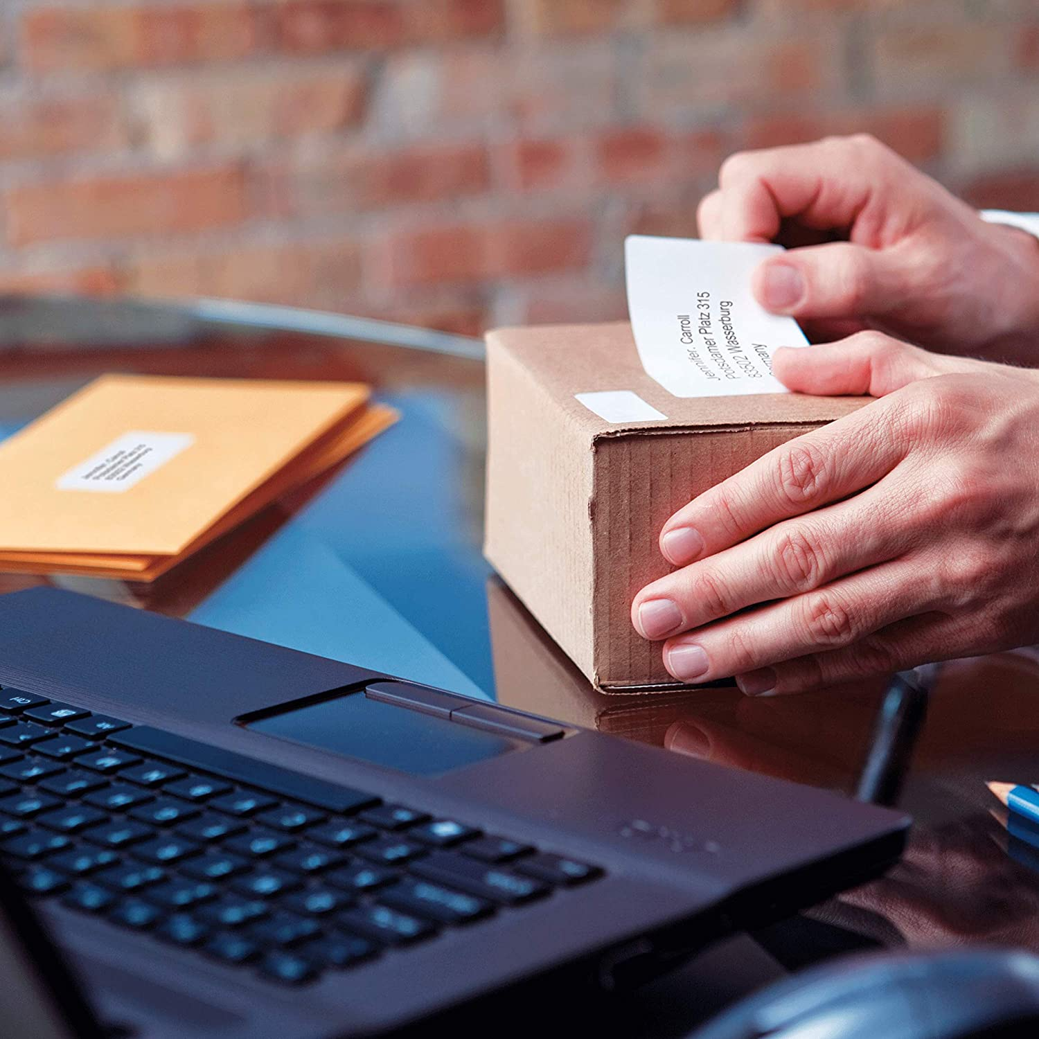 Placing freshly printed label on a shipping box in an office