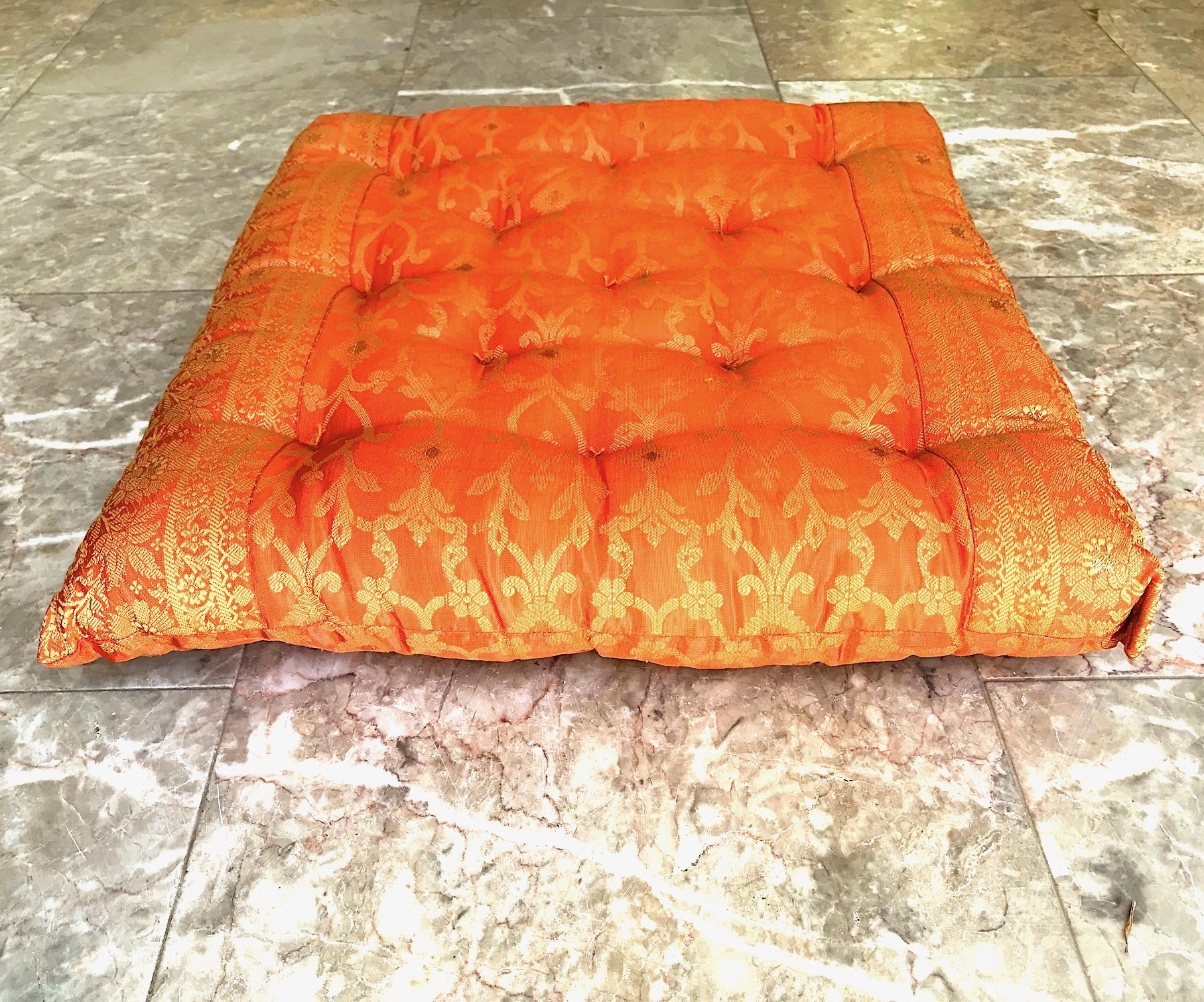 Worldcraft Industries Embroidered Orange Chair Cushion filled with natural cotton and hand tufted. The Kela Sari features a vine embroidered pattern and is trimmed with an intricate border.