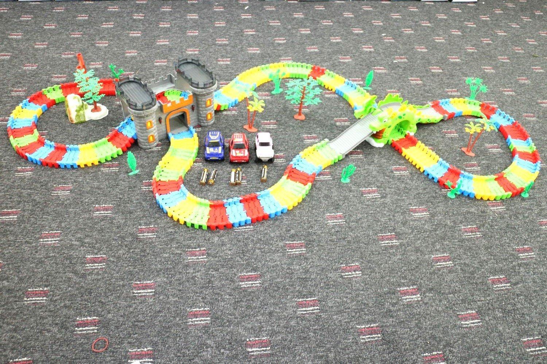 Tech Integrity  - Juego de rastreo de Carreras, Juguete Educativo 2 en 1, Dinosaurio y Castillo, con Palmeras, 3 x Jeeps para Coche, Rojo, Azul y Rosa + 9 x Pilas Super Alkaline