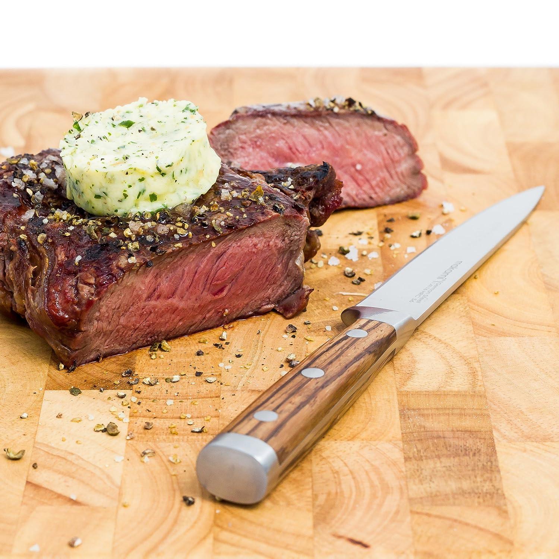 Makami Steakmesser auf Holzbrett neben Steak mit Kräuterbutter