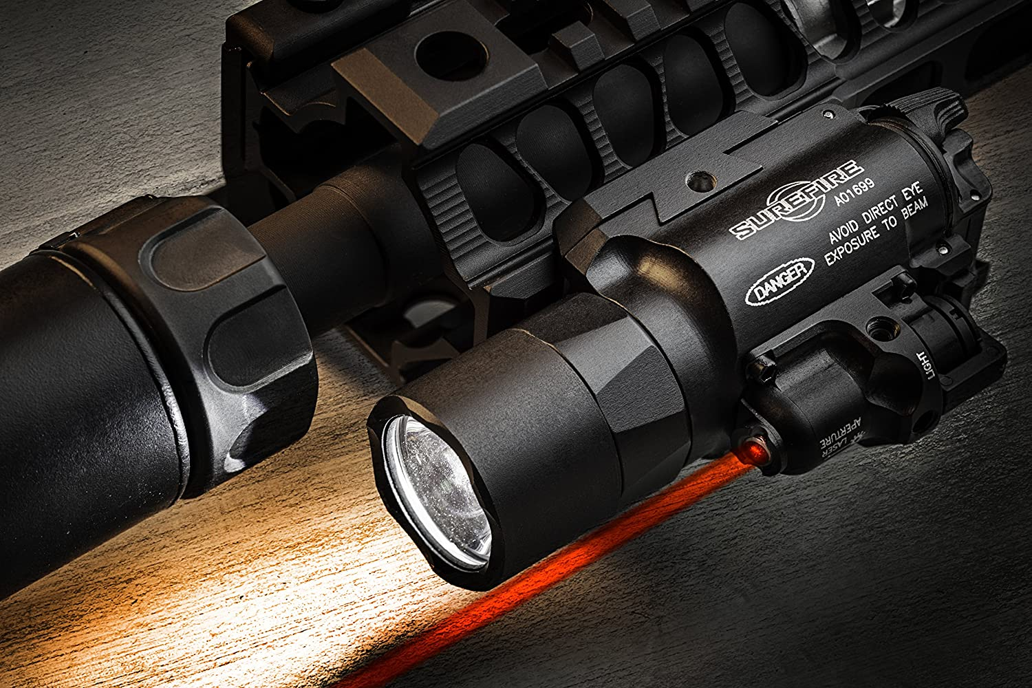 This is an image of a laser light with red beam attached on top of a pistol.
