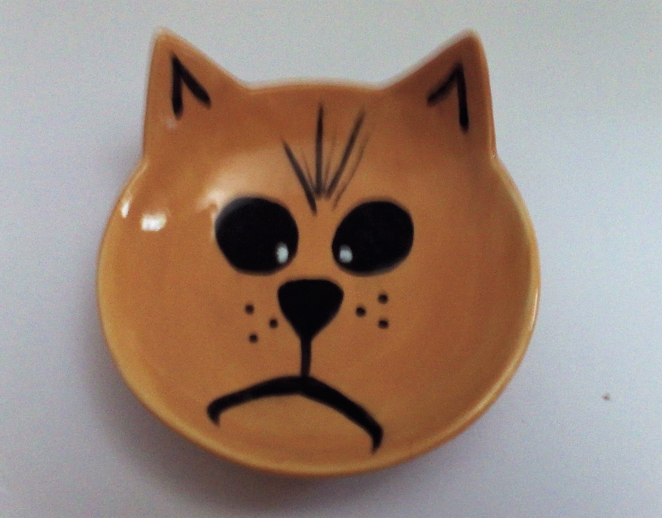 A happy cat water or feeding bowl in brown