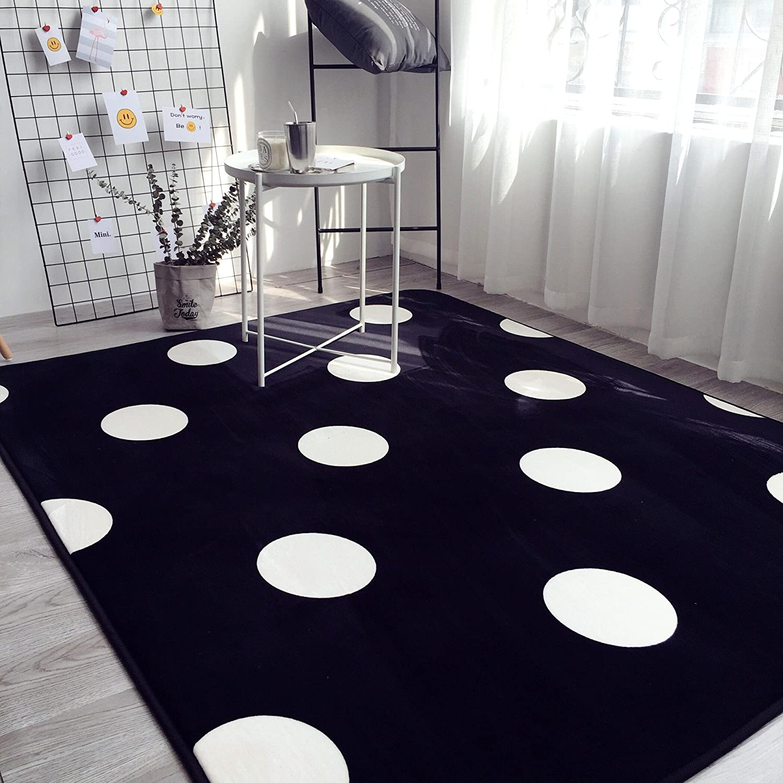 Black rug with white polka dots.