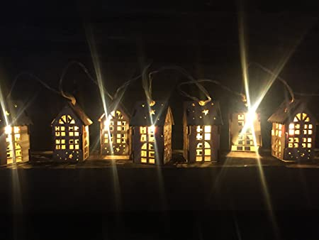 Night scene of wooden houses with christmas lights illustration