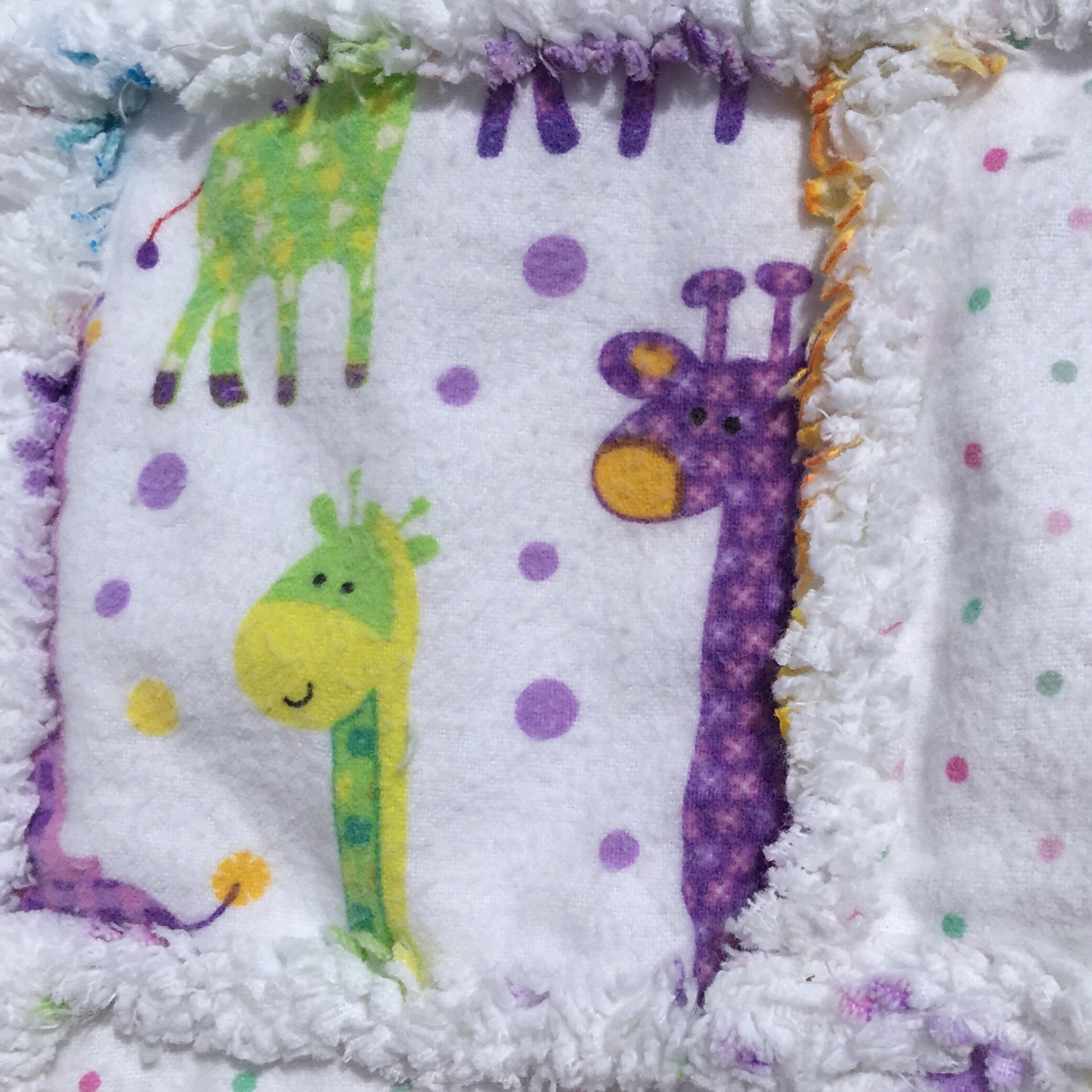 Colorful giraffes, bright multi-colored polka dots, and a white square border make tis a dazzling baby quilt