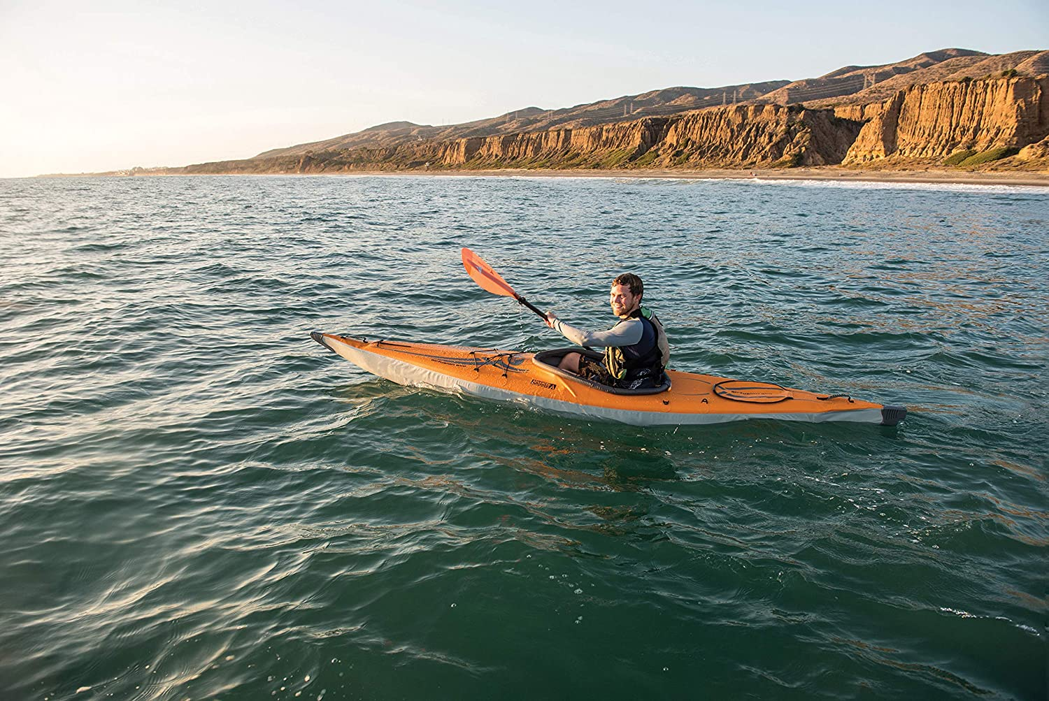 a person paddling in a kayak on an ocean