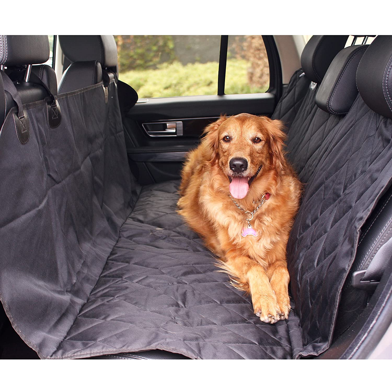 A golden retriever lies in the back seat of a car.
