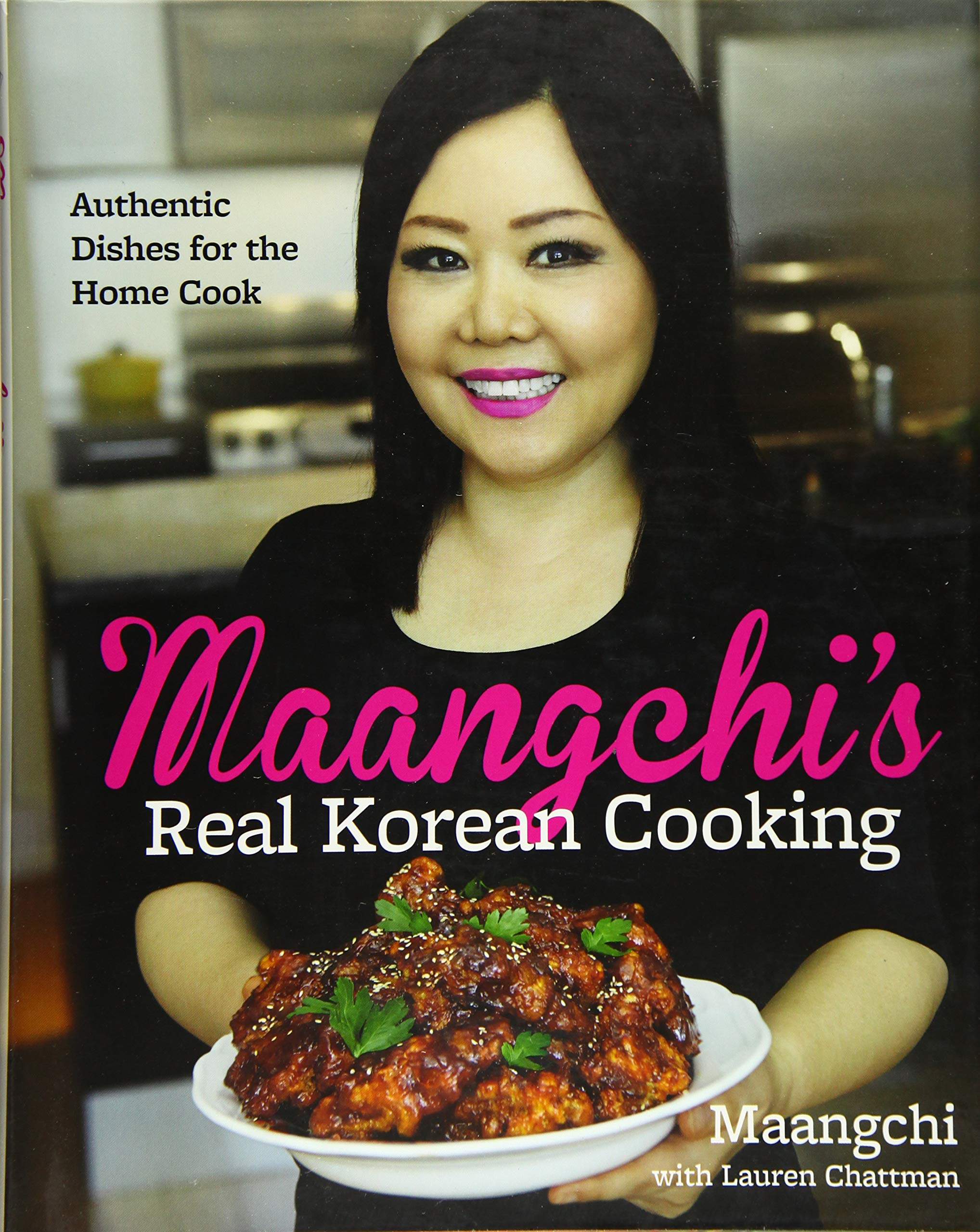 Book cover for Maangchi's Real Korean Cooking, which shows her in a black shirt with bright pink lipstick, holding a white bowl of Korean fried chicken garnished with sesame seeds and parsley.