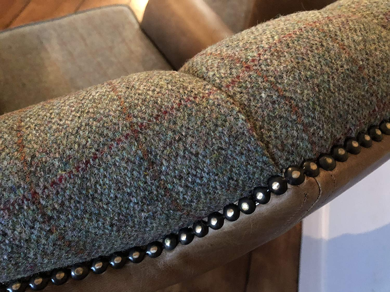 A pair of Chesterfield Queen Anne high back wing chairs and foot stool presented in vintage tan leather and green Harris tweed