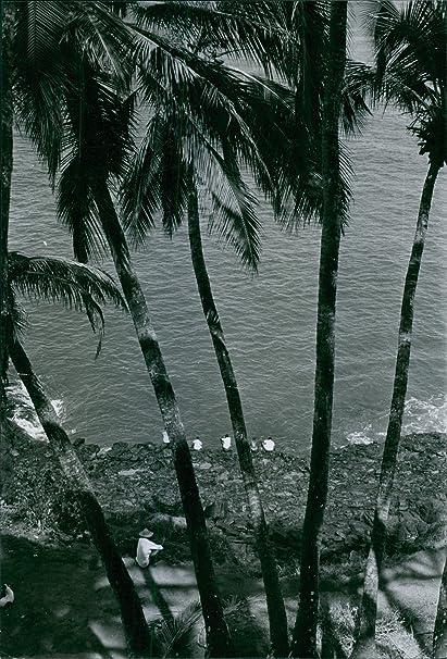 Vintage photo de personas sentado junto a la Orilla de Mar en el cobertizo de un