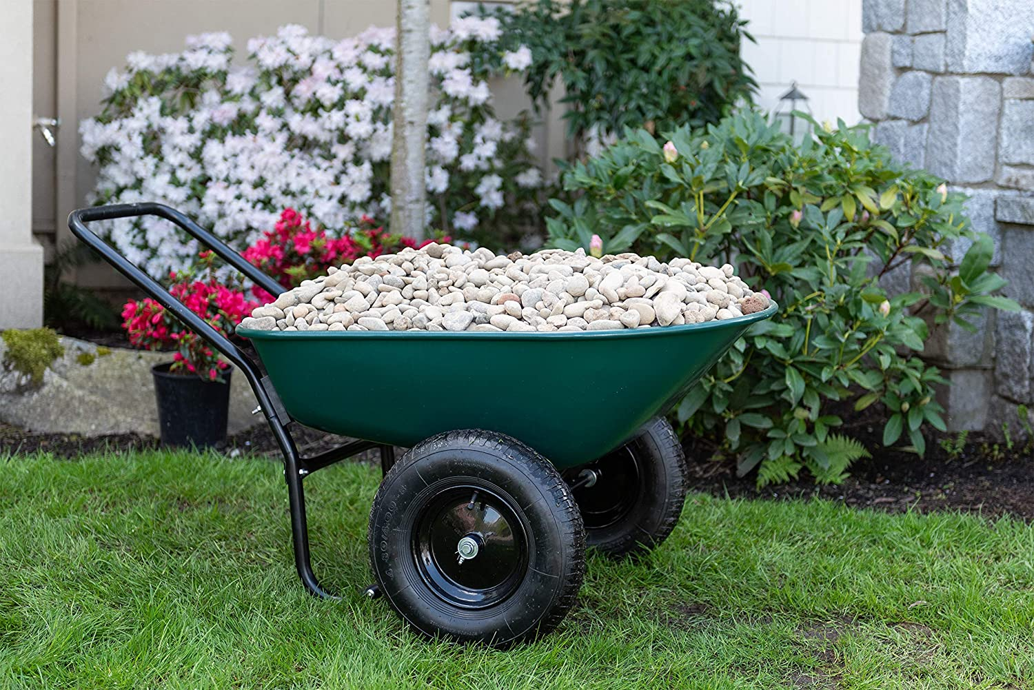 A perfect two wheel green wheel barrow filled with rocks, which are a type of mulch alternatives