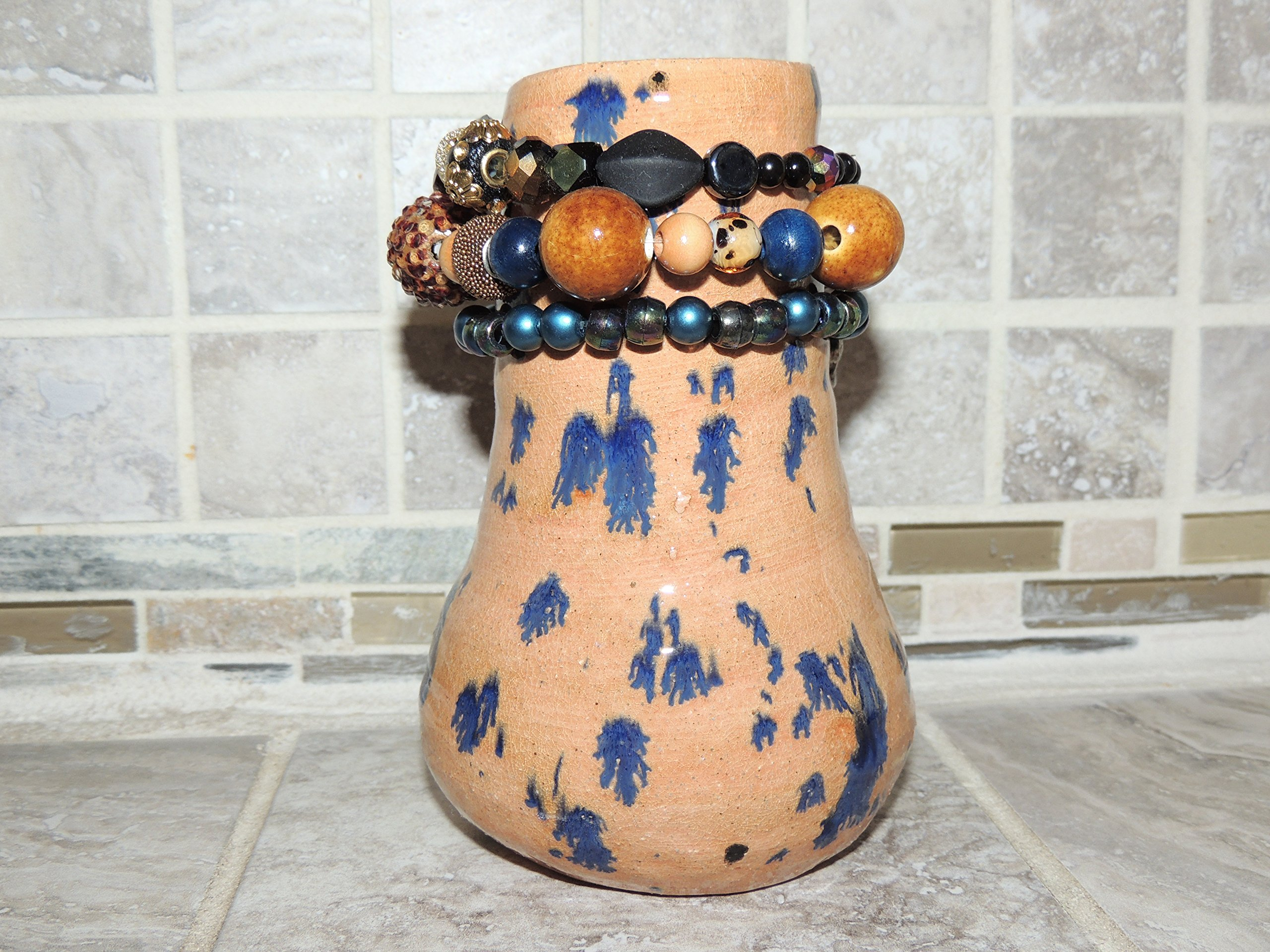 Hand Thrown Ceramic Vase. Beautiful Animal Print speckled glaze. Has hand strung beads around the top. Measures 4 x 6.