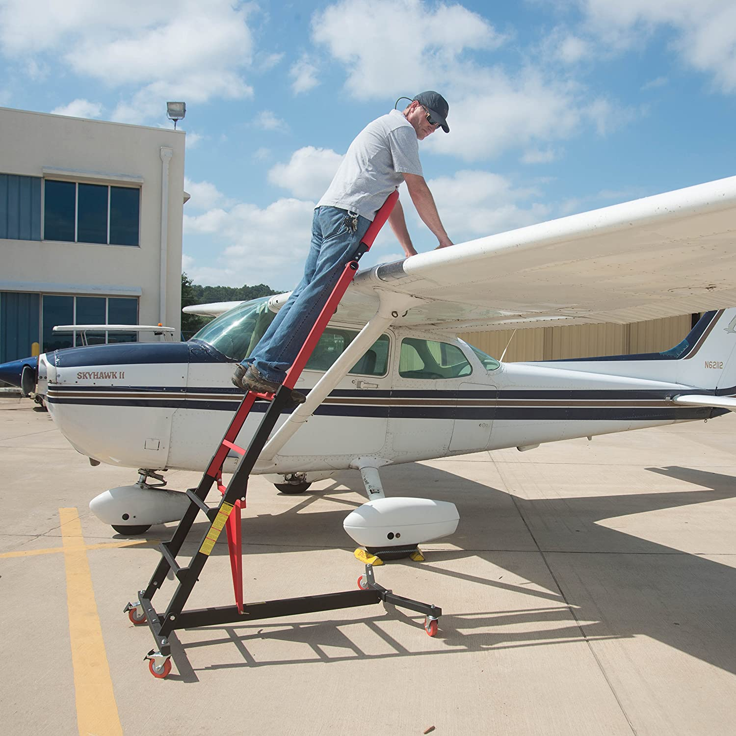 demonstration of pilot using traxion 3-700 to work on cessna wing