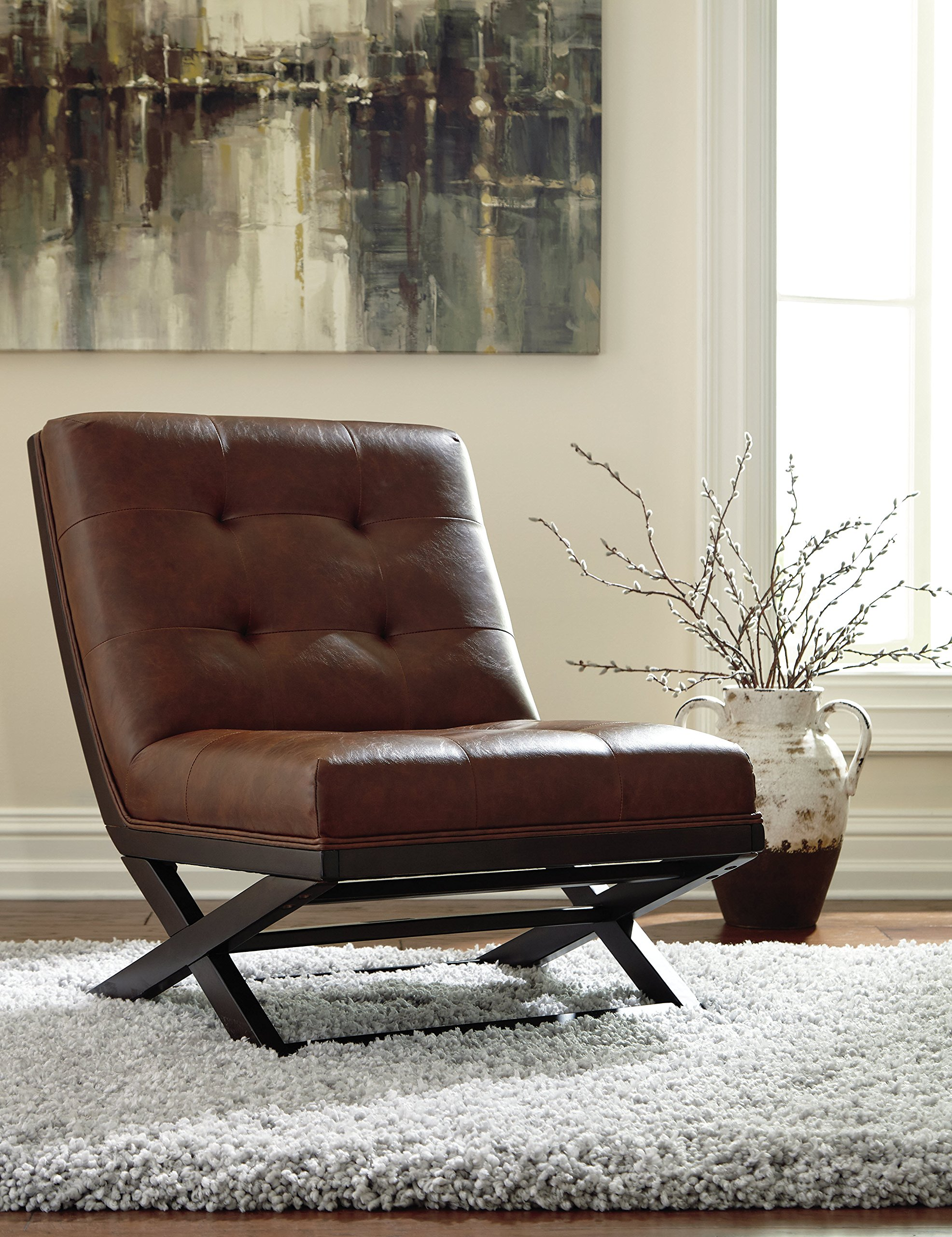 "Signature Design by Ashley - Sidewinder Accent Chair - Tufted Faux Leather - Brown - TUFTED ACCENT CHAIR: Sit back and enjoy high style. The faux leather exudes luxury, while the generous size lets you sprawl out. This armless chair is sure to make a bold statement HANDSOMELY CRAFTED: Sit back on high-resiliency foam cushions wrapped in faux leather upholstery. Designed with an exposed frame in a faux wood finish SCISSOR BASE: Inspired by the Barcelona chair, the ""X"" base and button tufting are chic details that set it apart from the rest - living-room-furniture, living-room, accent-chairs - 91kG0P1zIKL -"