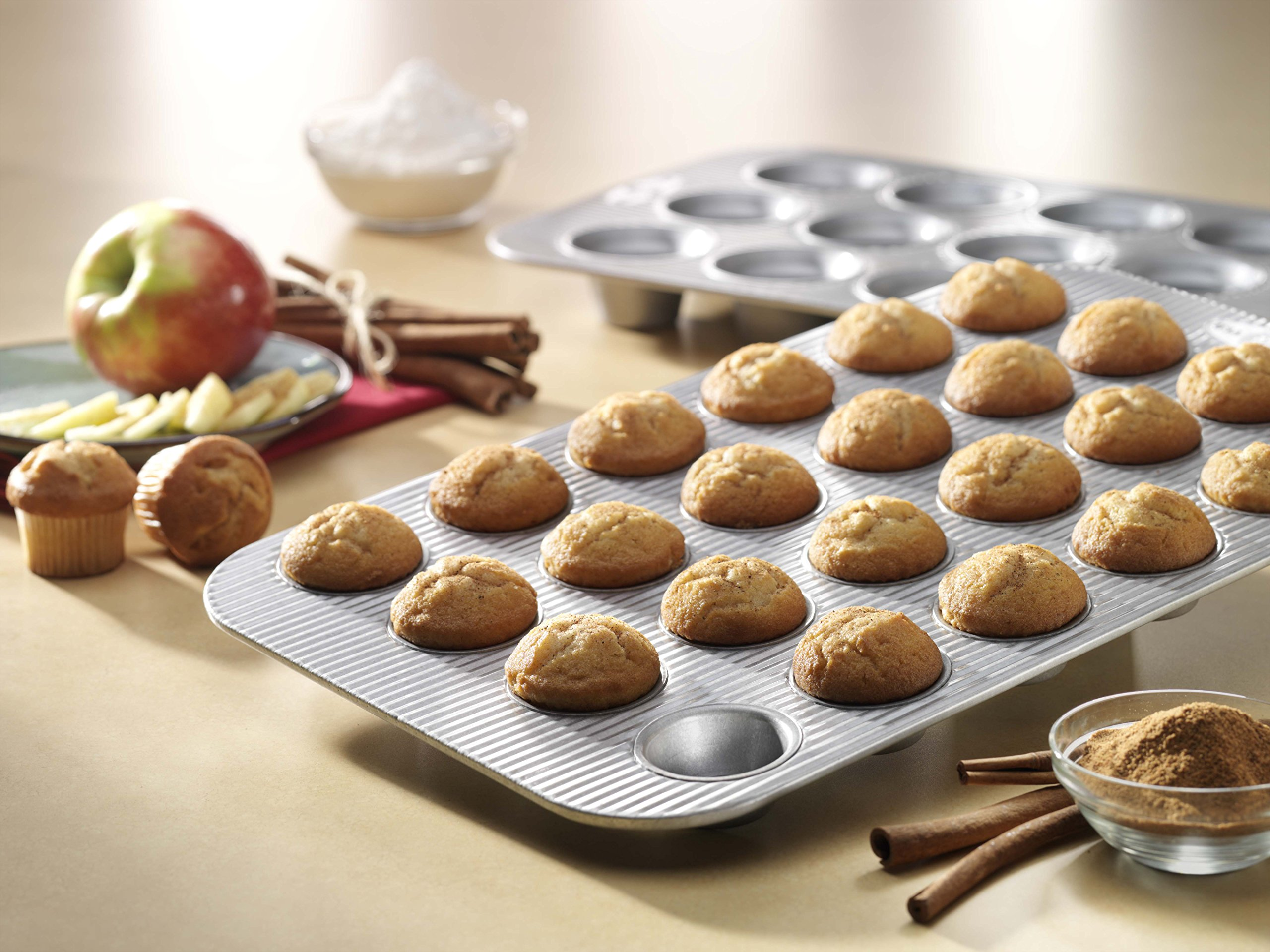 USA Pan Bakeware Mini Cupcake and Muffin Pan, 24 Well, Nonstick & Quick Release Coating, Made in the USA from Aluminized Steel 2 Mini Cupcake or Muffin Pan has 24 wells; commercial grade and heavy gauge aluminized steel with a lifetime warranty USA Pan baking pans feature Americoat which promotes quick release of baked-goods plus fast and easy clean up; wash with hot water, mild soap and gentle scrub brush or sponge Nonstick Americoat coating - a patented silicone coating which is PTFE, PFOA and BPA free - provides quick and easy release of all baked-goods and minimal easy clean up
