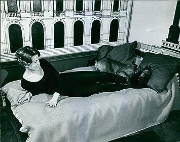 Vintage foto de Alexandra Stewart, actriz canadiense, sienta en cama con un perro.