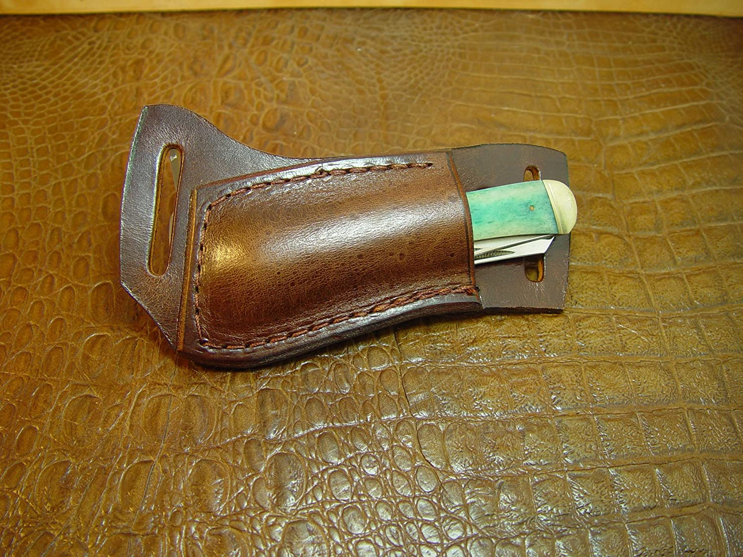 Custom Left-hand Cross Draw Trapper Style Folding Knife Sheath. Made Out of 10 Ounce Buffalo Hide Leather. Dyed Light Brown Sheath Only Knife Not Included.