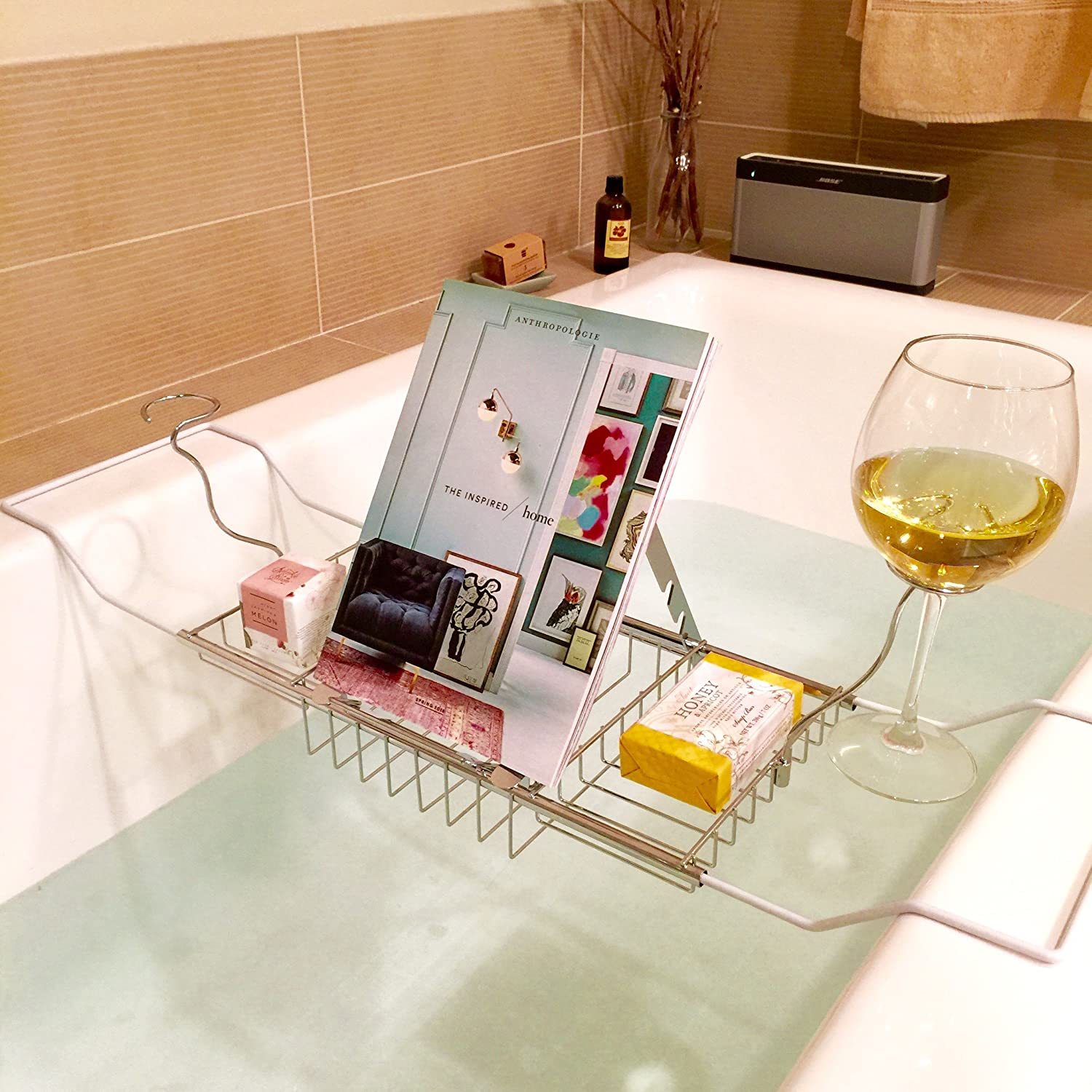 A picture of a bath caddy with a book and a glass of wine on it