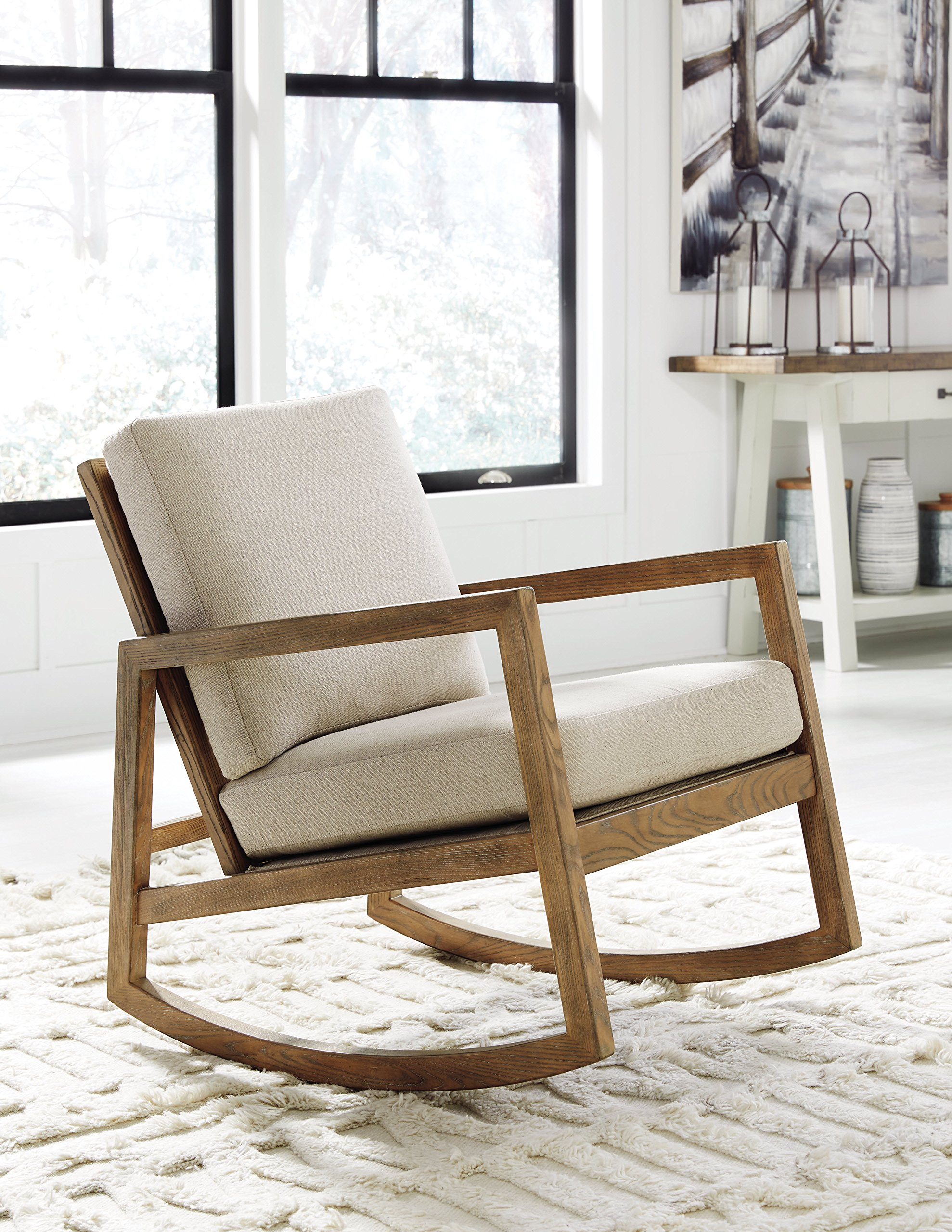 Ashley Furniture Signature Design - Novelda Rocking Accent Chair - Neutral Tan - Faux Wood Finish - LIVING ROOM ROCKING CHAIR: This accent chair touts sleek lines, but with subtle country-chic style. Warm, neutral hues play up the charm, while the plush cushions indulge you in modern comfort DEEP CUSHIONED COMFORT: Sit back and relax on high-resiliency foam cushions wrapped in a polyester/linen blend. Made complete with an exposed frame in a faux wood finish and squared armrests NATURAL HUES: Embracing materials in their natural form, the neutral fabric and light wooden tone easily matches a range of decor styles-whether yours is mid century, or filled with farmhouse flair - living-room-furniture, living-room, accent-chairs - 91ypTPcA OL -