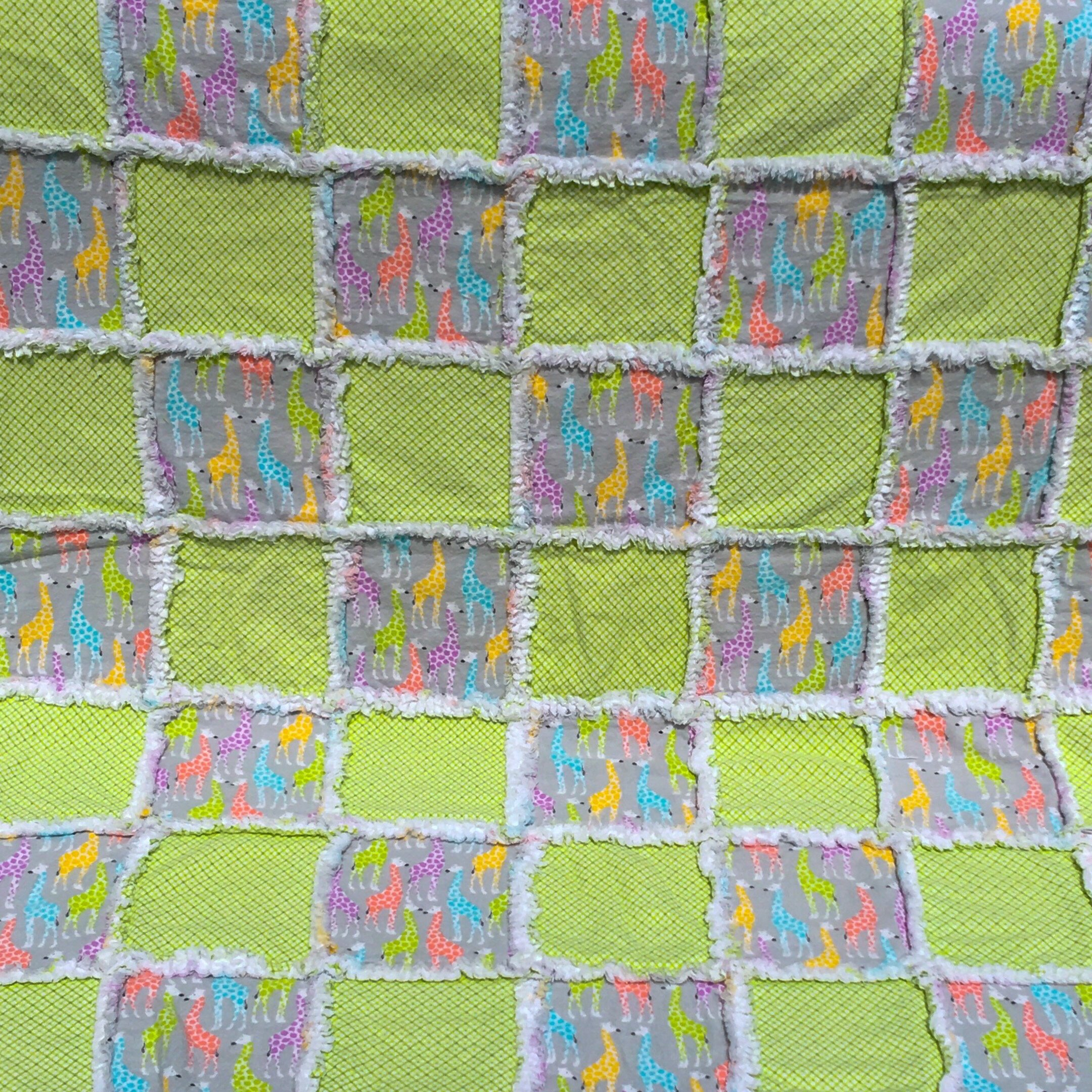 A rainbow of giraffes on a grey background with green and white tiny plaid squares flannel baby quilt