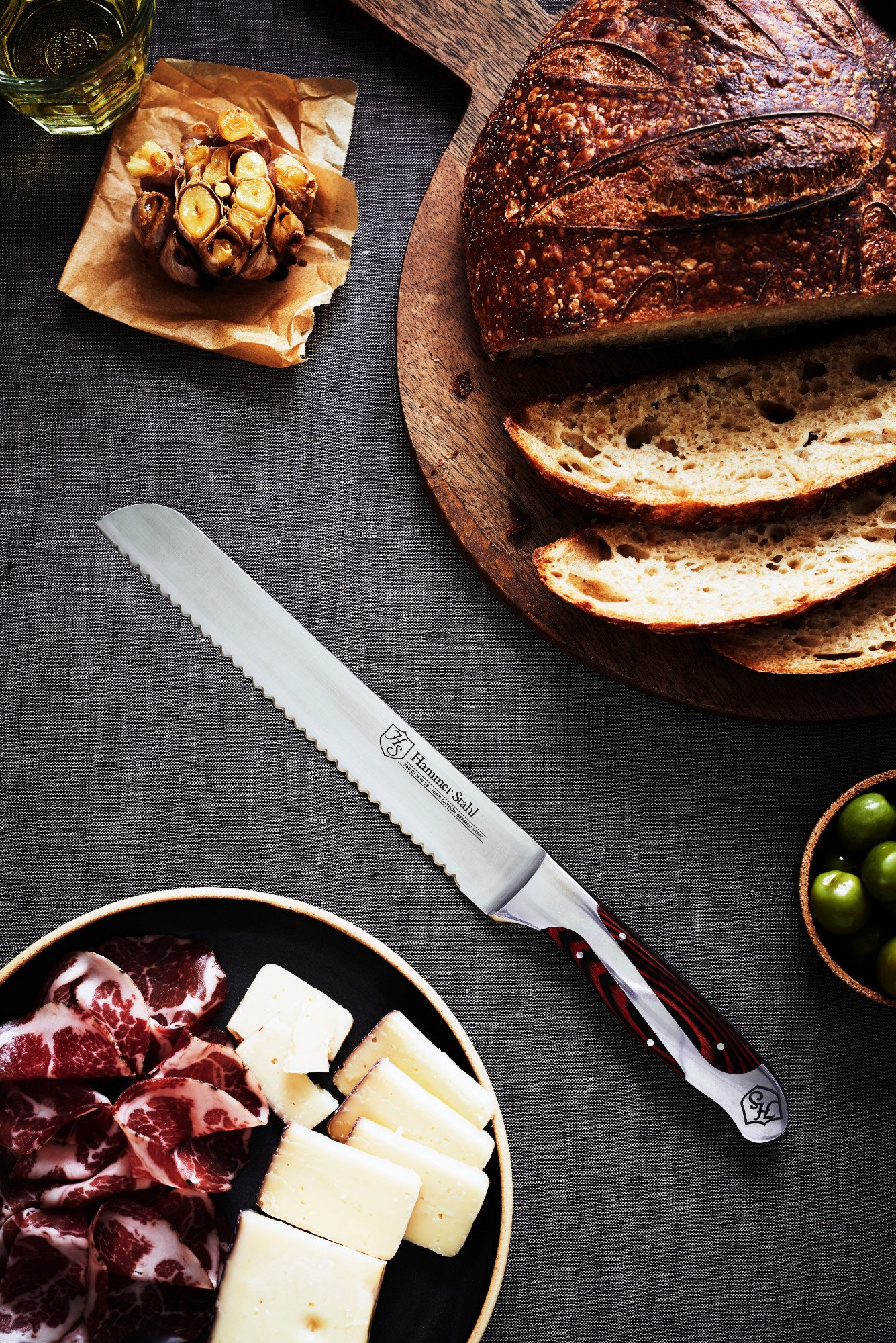 Hammer Stahl 8-Inch Bread Knife - Scallop Serrated Blade - High Carbon German Steel - Ergonomic Quad-Tang Pakkawood Handle 2 ✅ SCALLOPED EDGE - Rounded scallop-style serrated edge is extremely sharp, cleanly slicing instead of tearing. ✅ PREMIUM MATERIAL - Our cutlery is made from top-quality German X50CrMoV15 High Carbon Stainless Steel. It is forged and tempered to precise specifications and a Rockwell hardness of 55 - 57 that provides a superior edge and lasting durability. ✅ RAZOR SHARP - Each blade is precisely measured by laser for a world-class cutting edge. Every blade is sharpened to a 20 degree bevel angle.