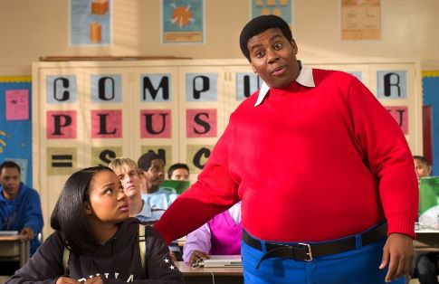 As Doris (Kyla Pratt) looks on in embarrassment, Fat Albert (Kenan Thompson) explains to her class why she needs his help.