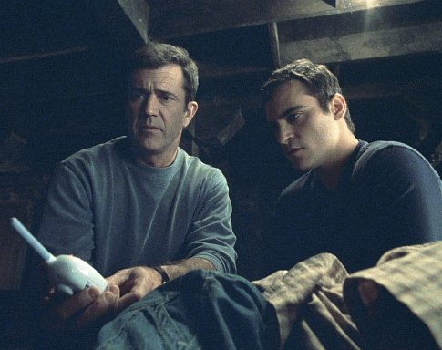 A baby monitor provides a message from above for Graham (Mel Gibson, left) and his brother, Merrill (Joaquin Phoenix, right).