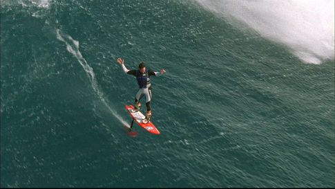 Rush Randle glides above the face of a wave, riding the new hydrofoil surfboard at Jaws - the famed big wave spot on Maui.