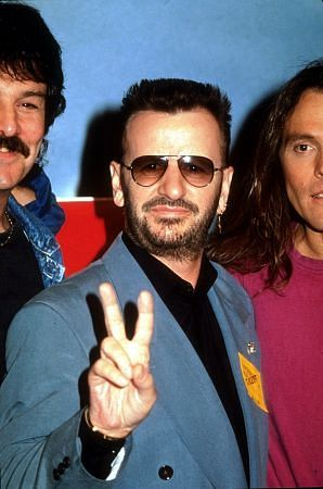 Ringo Star holding up a peace sign.