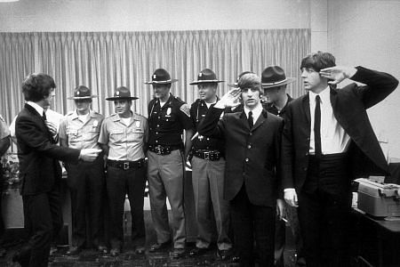 The Beatles (George Harrison, Ringo Starr, & Paul McCartney) in Indianapolis with officers as Ringo and Paul salute. c. 1964