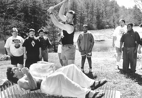 Demonstrating that his PerkiSystem total fitness program builds strong bodies, health nut Tony Perkis (Ben Stiller, supine) proves his point on a bed of nails as the awestruck campers witness Lars (Tom Hodges, center) smashing a block of ice on Tony's brick-hard stomach.