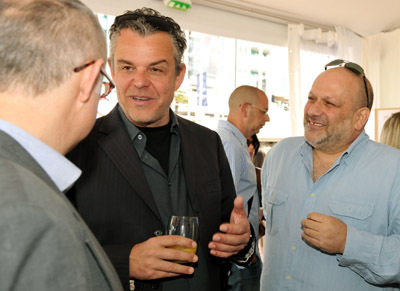 Director Eran Riklis (R) and actor Danny Huston (C) talk to guests as they attend the Danny Huston Press Breakfast held at the Moet Salon, Baoli Beach during the 63rd Annual International Cannes Film Festival on May 14, 2010 in Cannes, France.