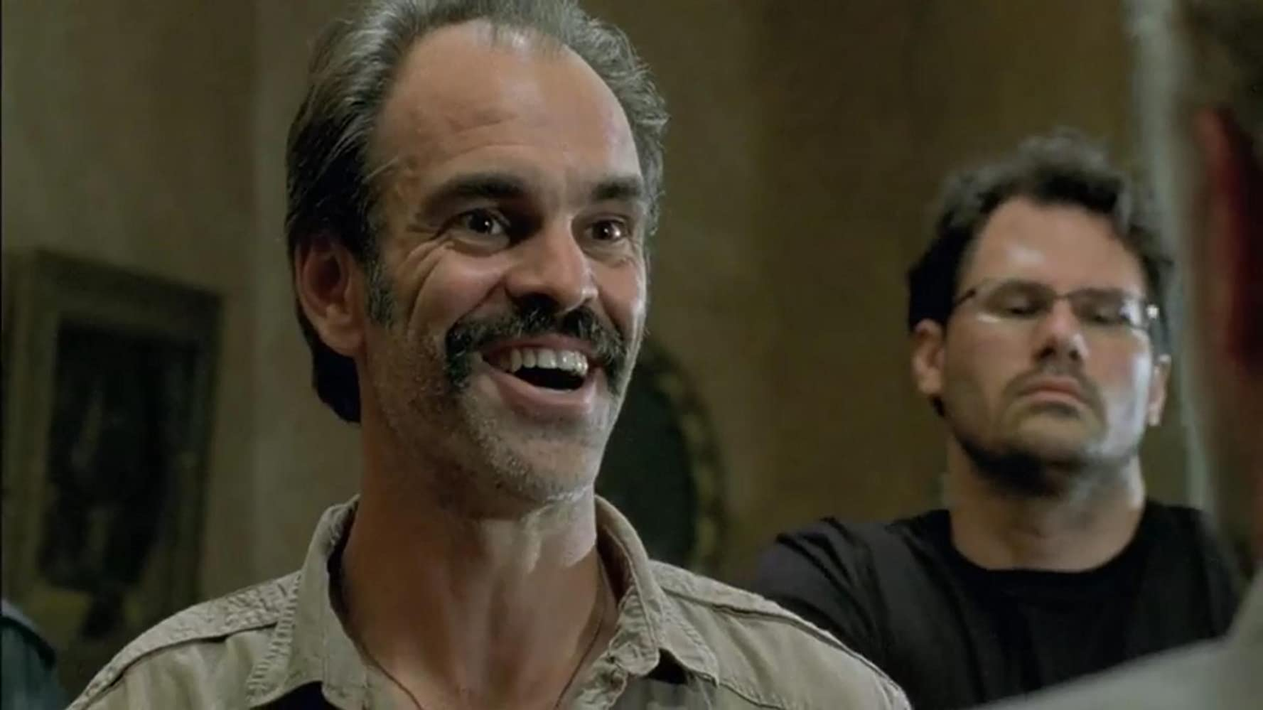 "Photo of Simon and an unnamed character from the TV series, ""The Walking Dead."" Simon is smiling maniacally, and the other guys is looking solemn and quiet with his eyes cast doen"