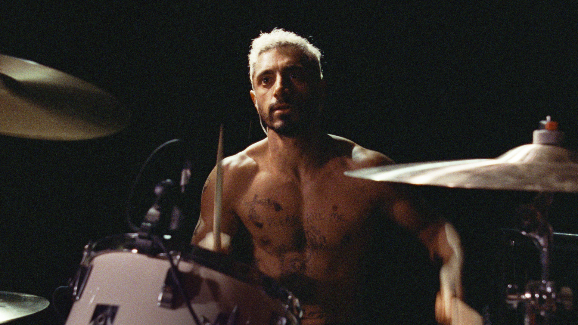 Image is from the film Sound of Metal (2019). A shirtless man, with a chest covered in tattoos, plays the drums. He looks angry.
