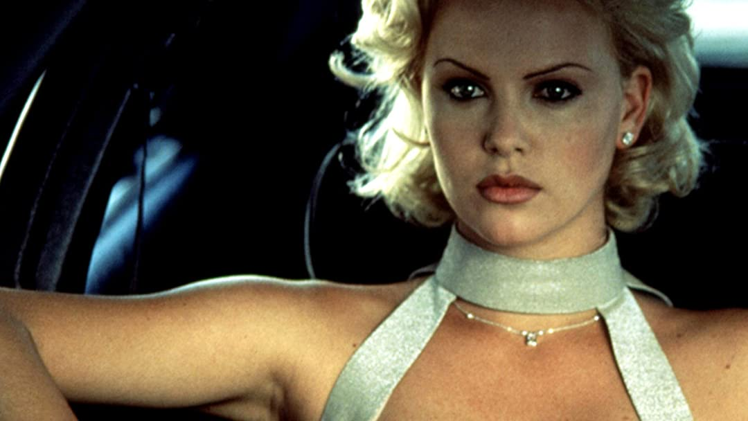 Image is from the film '2 Days in the Valley' (1996). A blonde woman wearing a silver dress sits in a car with a stern expression.